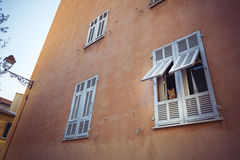 Ginger cat peering out ginger building in old town of Nice Royalty Free Stock Images