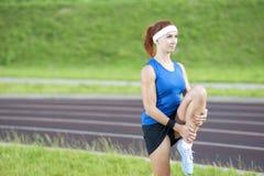 Ginger Caucasian Female em Sportgear atlético que tem os pés que esticam exercícios fora fotografia de stock