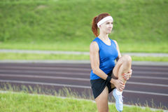Ginger Caucasian Female en Sportgear atlético que tiene piernas que estiran ejercicios al aire libre Fotografía de archivo