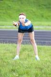 Ginger Caucasian Female pelirrojo joven en Sportgear atlético que tiene brazos que estiran Excercises combinado con el doblez del Imagenes de archivo