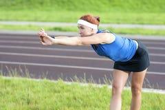 Ginger Caucasian Female pelirrojo joven en Sportgear atlético que hace los brazos que estiran Excercises al aire libre Imagenes de archivo