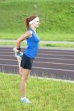 Ginger Caucasian Female pelirrojo joven en Sportgear atlético que tiene piernas que estiran ejercicios al aire libre Imágenes de archivo libres de regalías