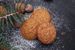 Ginger Christmas-Plätzchen auf einem schwarzen Brett mit Zuckerpulver und -Tannenzweig Kochen von recipie Stockfotografie