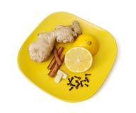 Ginger, cinnamon, lemon, garlic and cloves on the plate Stock Photos