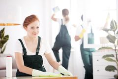 Cleaning lady dusting table. A ginger cleaning lady dusting a table and smiling stock image