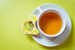 Ginger cookie and cup of tea on green background Stock Photos