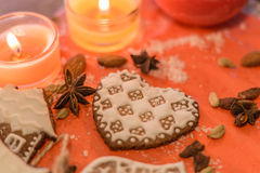 Ginger cookie in form of heart. Christmas ginger cookies covered with white icing, two orange candles and spices on a light brown wooden background and red stand Royalty Free Stock Photography