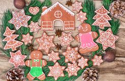 Ginger cookies. Gingerbread house, gingerbread man, stars and fir-tree on wooden background. royalty free stock photo