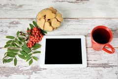 Ginger cookies hearts. Autumn atmosphere. A modern tablet. Rowan branch Royalty Free Stock Photo