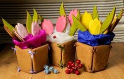 Ginger Cookies hecho en casa en la forma de tres cestas de flores del tulipán con las bayas en el fondo de madera primer foto de archivo