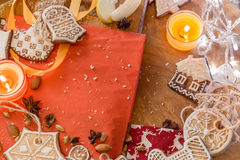 Ginger cookies with white icing on a red and brown wood background. Christmas ginger cookies covered with white icing on a light brown wooden background and red Royalty Free Stock Image