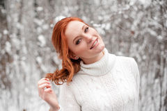 Ginger cute girl in white sweater in winter forest. Snow december in park. Christmas time. Happy New Year poster with beautiful woman royalty free stock photo
