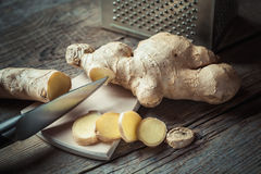 Ginger on cutting board and grater on kitchen table Royalty Free Stock Image