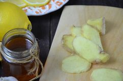 Ginger on cutting board, jar of honey, dried lemon slice, cinnamon and grater on kitchen table. Selective focus. Ginger on cutting board, jar of honey, lemon on Royalty Free Stock Photos