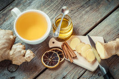 Ginger on cutting board, jar of honey, tea cup Stock Images