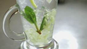 Ginger drink close up. Spoon stirring his tea with mint and lemon in a transparent glass, shot close-up stock footage