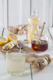 Ginger drink with honey and lemon. Ginger drink and the ingredients. Ginger, honey, lemon and syrup Stock Photography