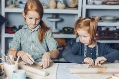 Ginger elder sister teaching to her little sister to create a clay dishes royalty free stock image