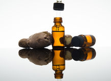 Ginger essential oil in amber bottle with ginger root and dropper Royalty Free Stock Photography