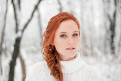 Ginger european girl in white sweater in winter forest. Snow december in park. Portrait. Christmas cute time. Royalty Free Stock Photos