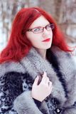 Woman with red hair in a gray fur coat. Ginger fashion woman in a gray fur coat, winter outdoor Royalty Free Stock Photo