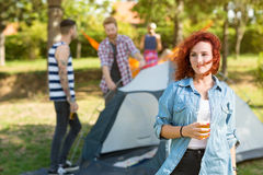 Ginger female with glass of beer stands in youth camp Royalty Free Stock Photo