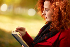 Ginger female reading book Stock Images