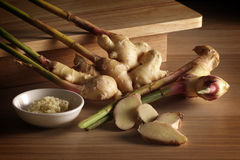 Ginger. Fresh whole ginger root with slices and grated ginger on wood background Stock Photography