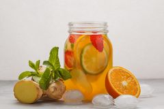 Ginger fruity ice tea with mint in a glass jar, white background