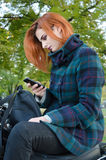 Ginger girl with cell phone Royalty Free Stock Image