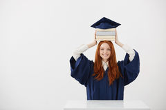 Ginger girl graduate smiling holding books on head under cap over white background. Copy space. Royalty Free Stock Photography