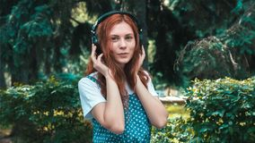 Freckled red-haired teenager listen music in big headphones royalty free stock photos