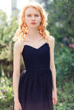 Ginger girl in long black dress on street .tinted photo. Ginger girl in long black dress on street at summer green tree.tinted photo Stock Photography