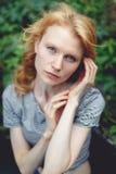 Ginger girl near green bush in summer, tinted photo Royalty Free Stock Photos