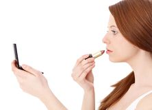 Ginger girl putting on lipstick Royalty Free Stock Photo