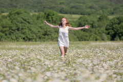 Ginger girl runs on meadow Stock Photography