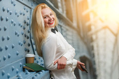Ginger girl in white shirt and black trousers with telephone royalty free stock image