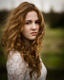 Ginger Girl in the Wind. Portrait of a girl with long curly ginger hair outside in the wind against a green background Stock Photography