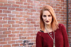 Ginger grungy woman and a brick wall. Fashion photo royalty free stock image