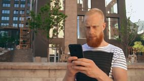 Ginger guy scrolling touch screen phone. Handsome bearded man using smartphone texting message. worker standing near building holding mobile sunny day summer stock video