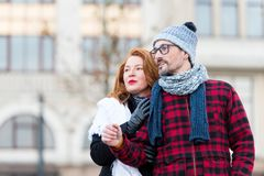 Ginger hair woman stoped man in glasses to ask the way. Aged couple looks at urban street life. Family couple walks on building background. Ginger hair women Royalty Free Stock Image