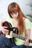 Ginger-haired girl playing guitar Stock Photos