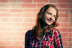 Ginger haired girl posing outdoors against red brick wall and looking away, a lot of copy-space Royalty Free Stock Photo