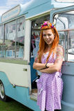 Ginger haired lady standing with vintage ice cream van. Young ginger haired lady wearing flower headband standing with vintage ice cream van. Portrait image with stock photography