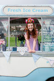 Ginger haired lady wearing vintage dress in ice cream van. Young ginger haired lady with facepaint smiling wearing vintage dress and flower headband stood in ice stock photography
