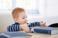 Ginger-haired little boy with encyclopedia smiling. Ginger-haired little boy looking at encyclopedia at table, smiling royalty free stock photos