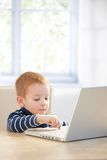 Ginger-haired toddler using laptop at home Royalty Free Stock Image