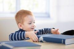 Ginger-haired weinig jongen met encyclopedie het glimlachen Royalty-vrije Stock Foto's