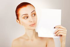 Ginger haired woman watches blank paper Stock Photo
