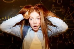 Not ready. Ginger head girl ruffling her long hair with confused expression Stock Image